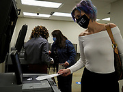 Courtney Huff places her ballot in the optical scanner on the first day of early voting in Ohio.