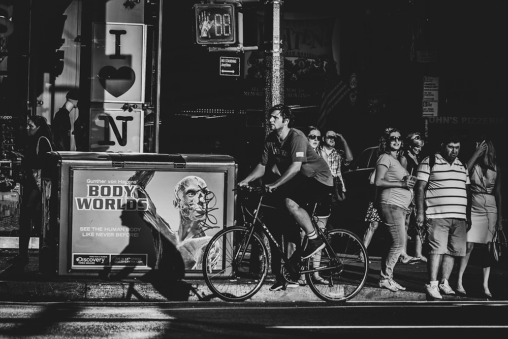 New York City, USA - July 6, 2016: On a busy street in Manhattan, a man cycles past an advertisement for Gunther von Hagens' Body Worlds exhibit.