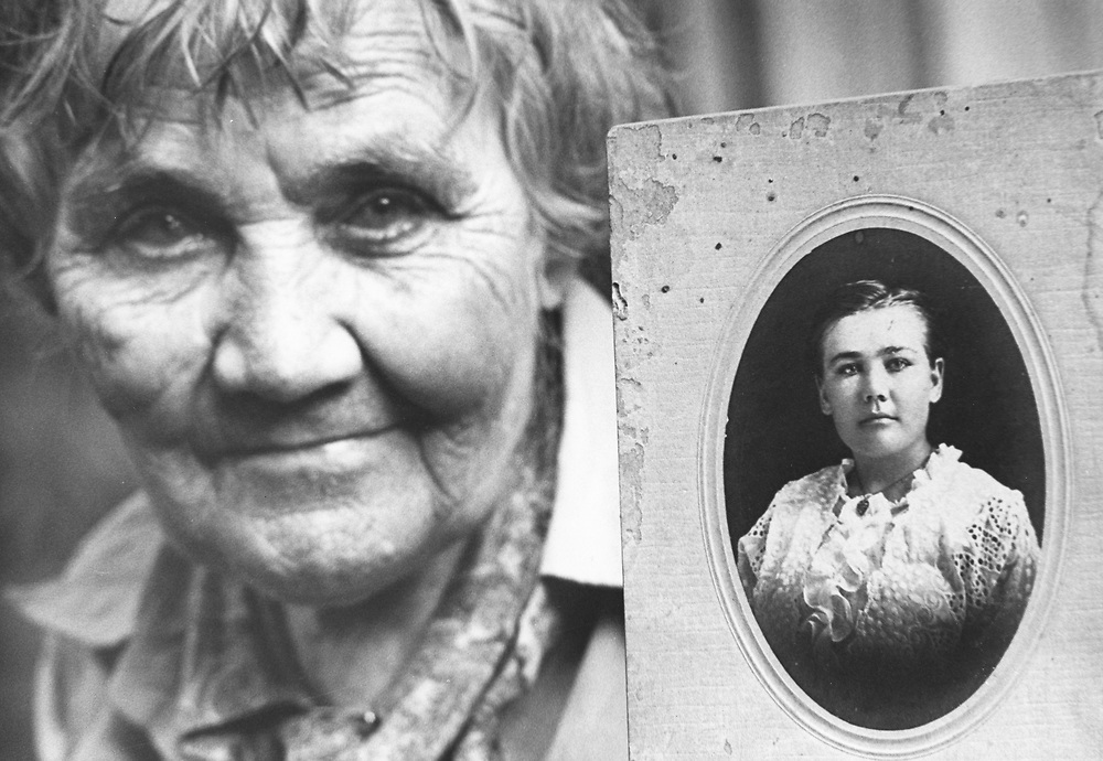 ©1978 woman with picture of her younger self, Hearne, Texas.