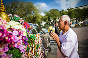 06 JANUARY 2013 - BANGKOK, THAILAND:  A man prays at the truck carrying a relic of the Buddha's hair during a service for the relic in Bangkok. The relic has been on display in Bangkok for about 10 years. There was a ceremony in Sanam Luang in Bangkok Sunday to honor the relic. People prayed for it and received blessings from Buddhist monks and Brahmin priests who presided over the service. The hair is being moved to Ayutthaya, where it will be displayed in a Buddhist temple. The piece of hair has been on loan to Thai Buddhists from a Buddhist temple in Sri Lanka.   PHOTO BY JACK KURTZ