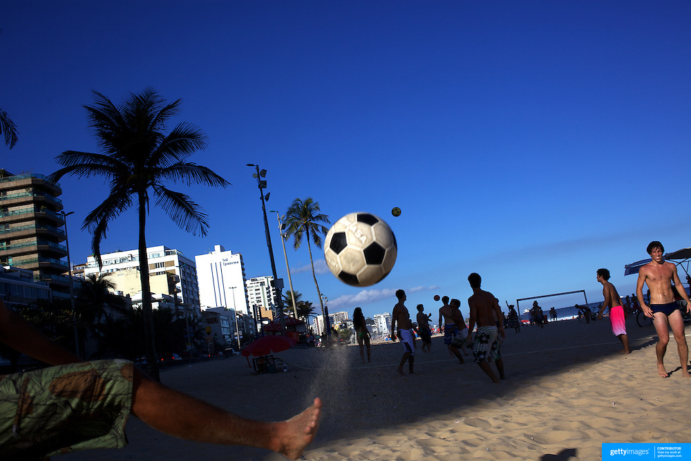 Locals practice foot volley, a hybrid game combining beach volley ball and football at Ipanema beach, Rio de Janeiro,  Brazil. 5th July 2010. Photo Tim Clayton..The beaches of Rio de Janeiro, provide the ultimate playground for locals and tourists alike. Beach activity is in abundance as beach volley ball, football and a hybrid of the two, foot volley, are played day and night along the length and breadth of Rio's beaches. .Volleyball nets and football posts stretch along the cities coastline and are a hive of activity particularly at it's most famous beaches Copacabana and Ipanema. .The warm waters of the Atlantic Ocean provide the ideal conditions for a variety of water sports. Walkways along the edge of the beaches along with exercise stations and cycleways encourage sporting activity, even an outdoor gym is available at the Parque Do Arpoador overlooking the ocean. .On Sunday's the main roads along the beaches of Copacabana, Leblon and Ipanema are closed to traffic bringing out thousands of people of all ages to walk, run, jog, ride, skateboard and cycle more than 10 km of beachside roadway. .This sports mad city is about to become a worldwide sporting focus as they play host to the world's biggest sporting events with Brazil hosting the next Fifa World Cup in 2014 and Rio de Janeiro hosting the Olympic Games in 2016...
