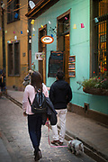 Two woman with dog walking on city street with old architecture, Valparasio, Chile