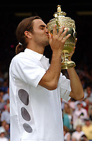 Roger Federer (Switzerland) kisses the Mens Singles Trophy after his straight sets victory over Mark Philippoussis (Australia) Wimbledon Tennis Championship, Day 13, 6/07/2003. Credit: Colorsport / Matthew Impey DIGITAL FILE ONLY