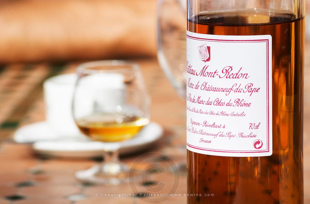 A snifter glass and A bottle of Chateau Mont Redon Vieux Marc de Chateauneuf, eau de vie de marc des cotes du Rhone. Spirit made from chateauneuf wine press residues. The restaurant Le Verger de Papes in Chateauneuf-du-Pape Vaucluse, Provence, France, Europe