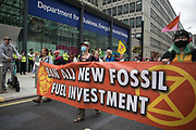 Environmental activists from Extinction Rebellion arrive at the Department for Business, Energy and Industrial Strategy BEIS at the end of a Stop The Harm march during the fourth day of Impossible Rebellion protests on 26th August 2021 in London, United Kingdom. Extinction Rebellion are calling on the UK government to cease all new fossil fuel investment with immediate effect.