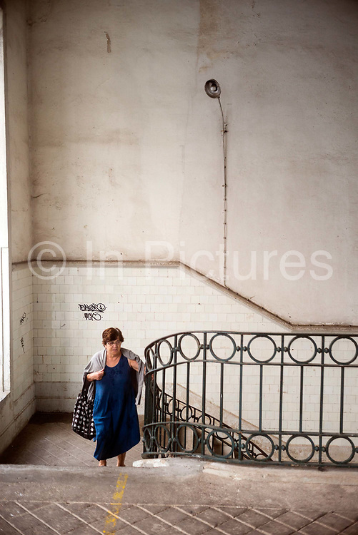 A woman climbs the stairs at the Mercado do Bolhão, Porto, Portugal. One of the most emblematic buildings of the city with wrought iron architecture over two floors, the market dates back to 1839.