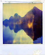 Old Polaroid of a perfect reflection of a Karstic landscape in Halong Bay, Quang Ninh Province, Vietnam, Southeast Asia. Colors of the old photograph bleed into each other.