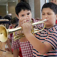 Angel Borrego, 9, watches Eduardo Chapa, 8, try to play the trumpet during the instrument petting zoo before the Houston Symphony Free Family Concert at the Ripley House, 06/04/04.  (Photo by Kim Christensen)