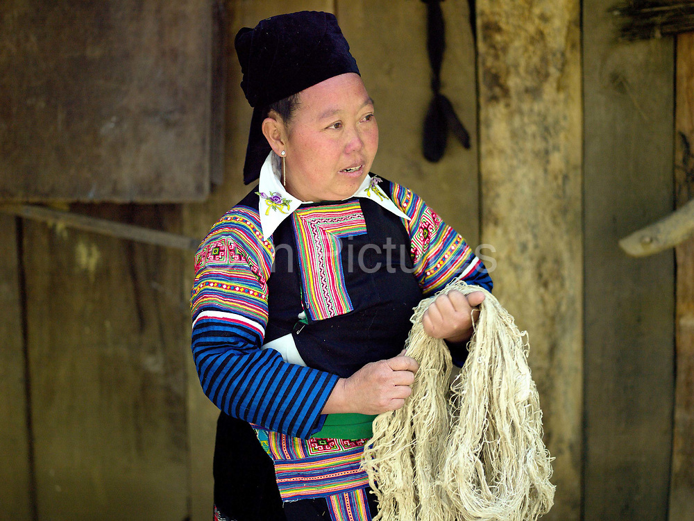 Wearing her traditional clothing, Tong, a Hmong Du woman holds a skein of hemp (cannabis sativa) fibre which she has produced herself, Ban Vieng Hang, Houaphan province, Lao PDR. Making hemp fabric is a long and laborious process; the end result is a strong durable cloth with qualities similar to linen which the Hmong Du women make into skirts for their traditional clothing. In Lao PDR, hemp is now only cultivated in remote mountainous areas of the north.