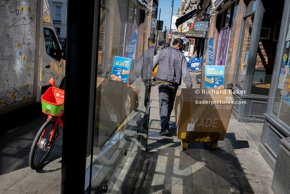 A discarded Lime rental bike stands in a bus shelter as delivery man pulls a box on a trolley during the third lockdown of the Coronavirus pandemic, on 29th March 2021, in London, England.