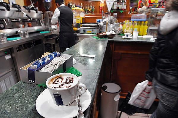 Italie, Napels, 7-3-2008..Cappucino in een café,cafe. de barman heeft de cacoa in de vorm van een lacvhend gezicht uitgestrooid.  De stad weet met zijn afval geen raad meer en in het hele gebied liggen illegale hopen afval. Een nieuwe vuilverbrandingsoven is pas in 2009 bedrijfsklaar. Tot die tijd heeft de maffia, camorra grote invloed op de afvalverwerking van deze stad...Industrieel afval en huishoudelijk afval veroorzaken grote water en bodemvervuiling, terwijl de streek een belangrijk tuinbouwgebied is...Foto: Flip Franssen