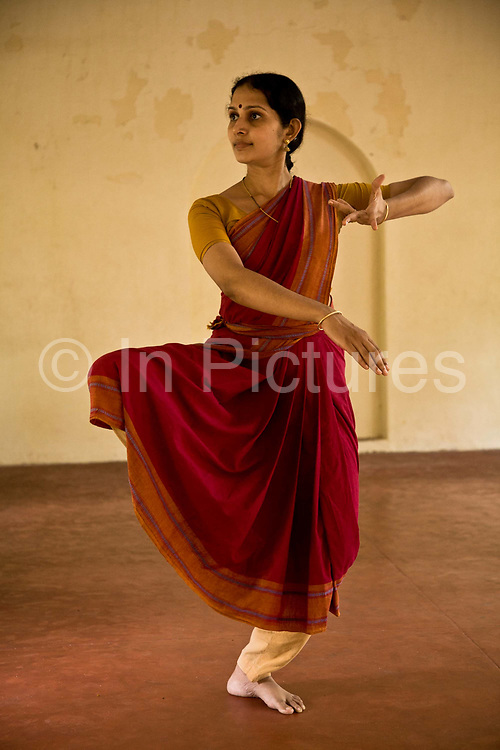 """Ganga Thampi, teaches young   dancers  movement, rhythm and expression, known as """"nritya"""" and seen here a lesson in """"abhinaya"""", or stylized expressions at the traditional and highly prestigious Kalakshetra school for the arts, Chennai. The school was founded in 1936 and due to its exacting and demanding schedule is considered India's formost classical dance academy of this ancient cultural art heritage that is informally known as """"temple dancing"""" and that dates back to the Natya Shastra, the 2000 year old text that lays down the principles of Indian dramatic theory and performance. Tamil Nadu, India"""