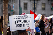 """San Francisco, USA. 19th January, 2019. The Women's March San Francisco begins with a rally at Civic Center Plaza in front of City Hall. A protester carries a sign through the plaza questioning, """"Who's the real 'nonessential worker'? Furlough Trump!"""" Credit: Shelly Rivoli/Alamy Live News"""