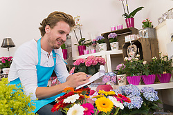 Mid adult man checking flowers in shop, smiling