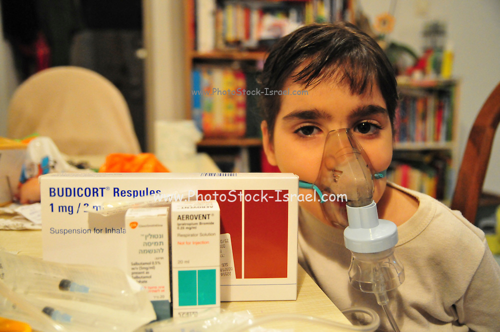 Health - young girl of 8 suffers from Asthma oxygen humidifier inhaler helps her breath various drugs in the foreground - Model Release available