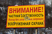 """Altai Region, Siberia, Russia, 25/02/2011..Sign at the entrance to the area of the first casino at the proposed Siberian Coin casino project in the Altai mountains. The sign reads: """"Warning! Private territory - no entry without invitation. Armed guards"""", and appears to have been damaged by bullets."""