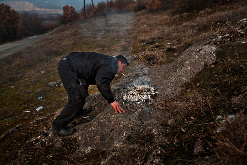 Uros Popovic lights his cigarette from the embers of a Christmas Eve bonfire near Velika Hoca, Kosovo. January 2011.