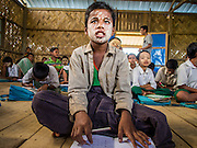 06 NOVEMBER 2014 - SITTWE, RAKHINE, MYANMAR: A boy in a school for Rohingya IDPs sits on the floor in the classroom. After sectarian violence devastated Rohingya communities and left hundreds of Rohingya dead in 2012, the government of Myanmar forced more than 140,000 Rohingya Muslims who used to live in and around Sittwe, Myanmar, into squalid Internal Displaced Persons camps. The government says the Rohingya are not Burmese citizens, that they are illegal immigrants from Bangladesh. The Bangladesh government says the Rohingya are Burmese and the Rohingya insist that they have lived in Burma for generations. The camps are about 20 minutes from Sittwe but the Rohingya who live in the camps are not allowed to leave without government permission. They are not allowed to work outside the camps, they are not allowed to go to Sittwe to use the hospital, go to school or do business. The camps have no electricity. Water is delivered through community wells. There are small schools funded by NOGs in the camps and a few private clinics but medical care is costly and not reliable.   PHOTO BY JACK KURTZ