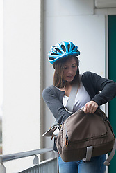 Young woman with bike helmet going out of the flat, Freiburg im Breisgau, Baden-Wuerttemberg, Germany