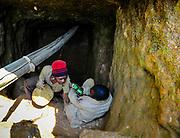 Gold mine in South Kivu, DRC Congo. A miner salutes a collegue while hauling a bag of ore through the shaft tunnel he works. Above his head runs an oxigen supply hose that is supposed to prevent asphyxiation. Murale, South Kivu, DRC. August 21, 2010.<br /> Un creuseur parle avec un collegue et monte un lourd sac de minerai d'or à travers le tunnel de la mine. Au-dessus de sa tête court un tuyau d'alimentation en oxygène censé empêcher l'asphyxie. Murale, Sud-Kivu, RDC. 21 août 2010.