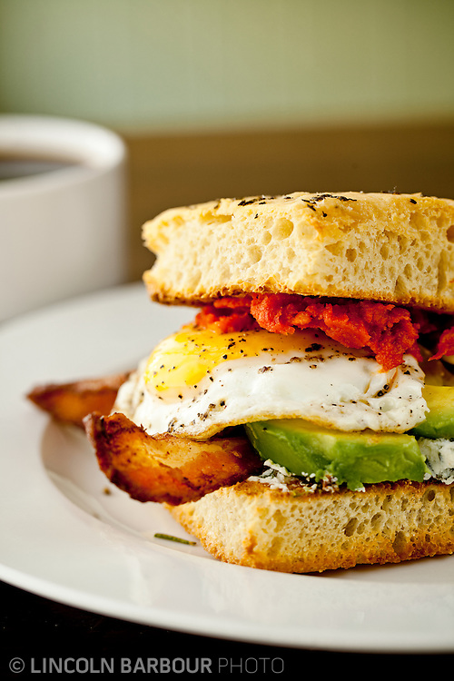 A delicious fried egg sandwich with bacon and avocado on what looks like a homemade biscuit with homemade ketchup.  Sitting on a white plate with coffee in the background out of focus