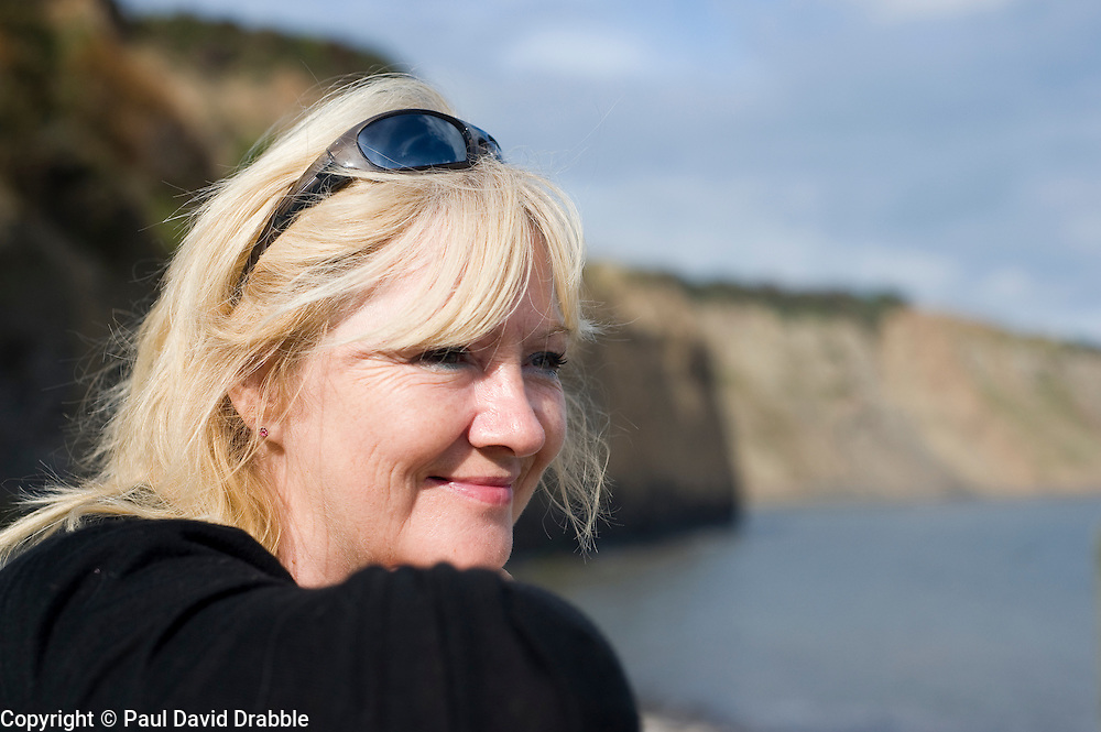 Attractive blonde older Woman looks out to sea over Robin Hoods Bay north Yorkshire.