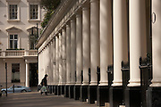 Resident arrives home under immaculate Doric columns of the classic Victorian properties in Eaton Square Belgravia, SW1