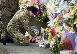 © London News Pictures. 31/05/2013. Woolwich, UK. A Cadet from the Royal Artillery barracks in Woolwich lighting a candle at the scene where Drummer Lee Rigby was killed in Woolwich, South East London. A group of cadets laid flowers and paid their respects. Photo credit: Ben Cawthra/LNP