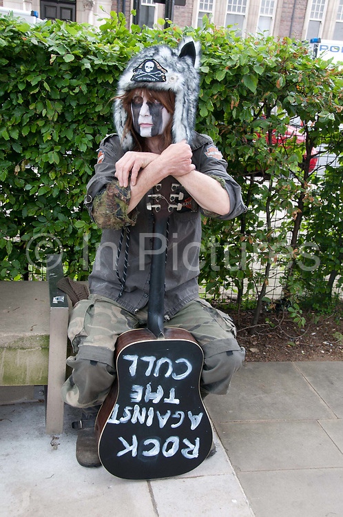 Protest against the proposed cull of badgers June 1st 2013. A man wearing a badger hat holds a guitar on which is written 'Rock against the Cull'.