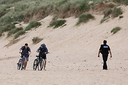© Licensed to London News Pictures. 21/05/2020. Padstow, UK. A police officer passes two cyclists on Constantine Bay beach in Cornwall during a spell of hot weather. Photo credit : Tom Nicholson/LNP