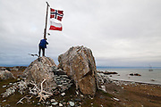 A man raises the Polish and Norwegian flags on a flagpole outside the  Polish research station in Hyttevika, Svalbard.