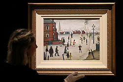 "© Licensed to London News Pictures. 12/11/2018. London, UK. A staff member hangs ""Rounders"" oil on panel by Laurence Stephen Lowry R.A. (British, 1887-1976). (Estimate £400,000-600,000).<br /> Bonhams Modern British and Irish Art photocall. Auction to be held on 14 November 2018. Photo credit: Dinendra Haria/LNP"
