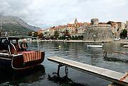 Man repairs fishing nets on boat, Korcula old town in background. Island of Korcula, Croatia