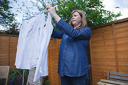 Pregnant woman hanging out washing.