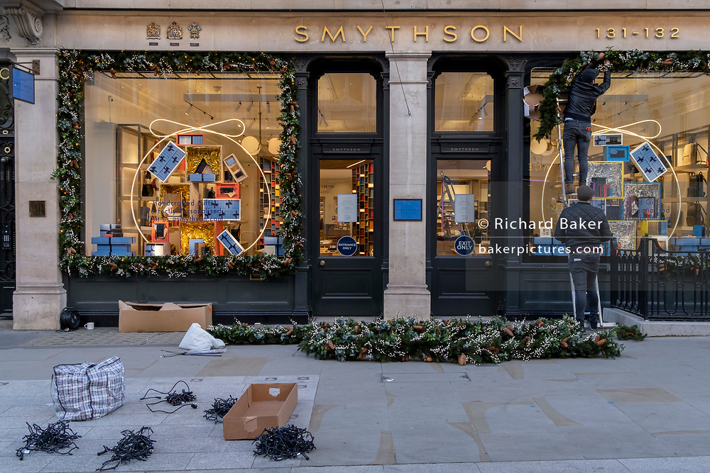 Contractors install Christmas decorations to the frontage of Bond Street retailer Smythsons as the second lockdown of the Coronavirus pandemic comes to a end, and a day before London enters the Tier 2 restriction when retailers will be allowed to once again re-open for the run-up to Christmas, on 1st December 2020, in London, England.