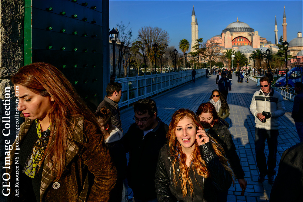 Against the backdrop of Hagia Sophia or the Church of the Holy Wisdom former Byzantine church turned Ottoman Empire mosque  tourists enter the Blue Mosque, called the Sultanahmet Camii in Turkish, in Istanbul's historic Sultanahmet District or Sultanahmet Square.