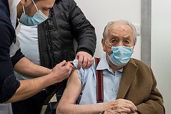 © Licensed to London News Pictures. 15/01/2021. LONDON, UK.  A vaccinator gives Lewis Fox, aged 98, a coronavirus vaccination at Cullimore Chemist in Edgware, north west London.  Cullimore Chemist is one of 6 community pharmacy pilot sites across the country offering coronavirus vaccinations, with 200 more to come online in the next two weeks.  Three special purpose consulting rooms have been constructed, staffed by qualified vaccinators to administer the Oxford-AstraZeneca vaccine.  Proprietor Hassan Khan expects to be able to offer 1,200 jabs per week, but the current problem is a bottleneck in vaccine supply.  Photo credit: Stephen Chung/LNP