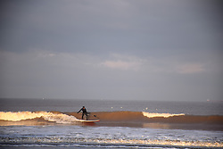 Paddle boarding in the winter sunshine, Cromer, Norfolk UK Dec 2020