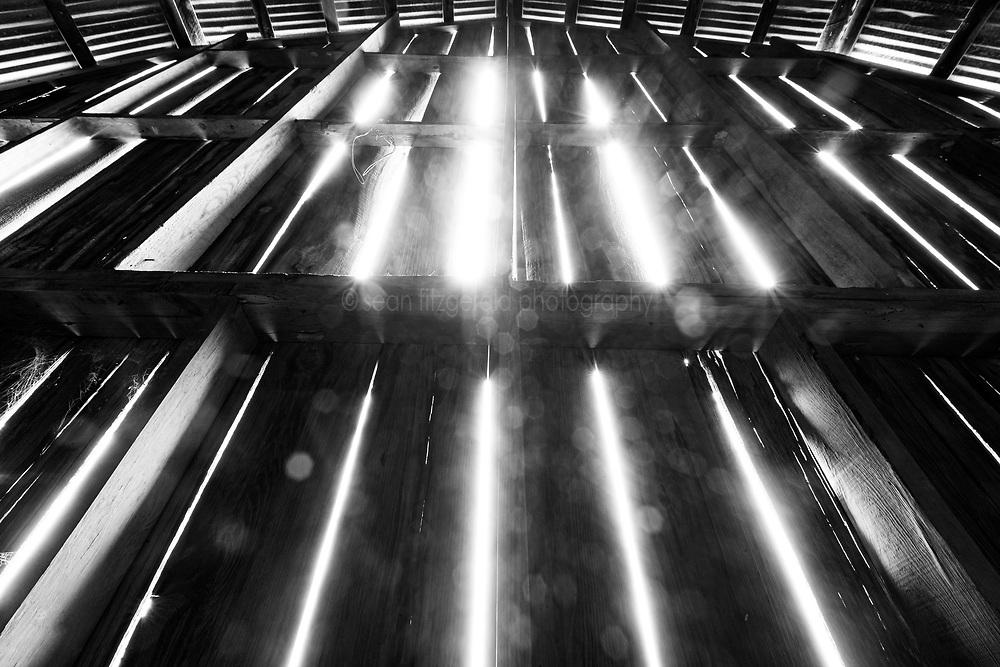 Light through slats of weathered barn, Muleshoe Historic Farm, Hill Country, Comfort, Texas, USA.