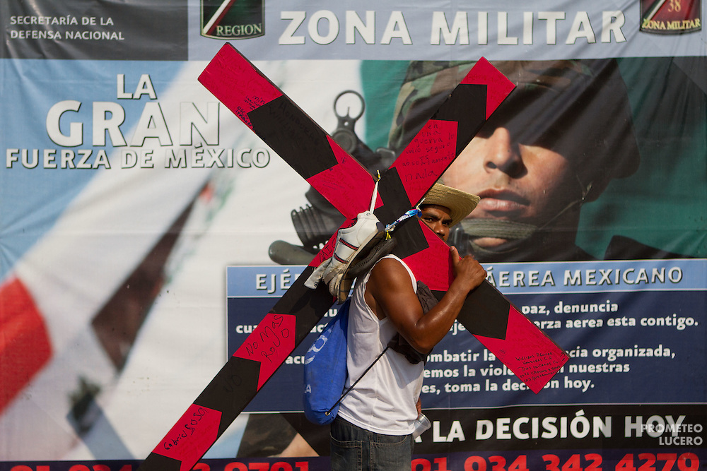 """A central american migrant carries a cross during the """"Viacrucis migrante"""" in front of the  38A Military Zone, on April 6th, 2012. (Photo: Prometeo Lucero)"""