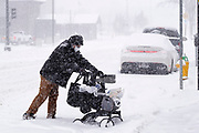 29 DECEMBER 2020 - DES MOINES, IOWA: A person tries to push their groceries through snow packed streets in Des Moines during the heaviest snowfall so far of the 2020-21 winter. Des Moines was expected to get about 8 inches of snow before Wednesday morning. Statewide, across Iowa, more than 900 snowplows have been called out to clear the roads.      PHOTO BY JACK KURTZ
