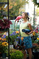 Young woman with yoga mat smelling flowers at street vender.