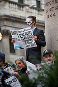 Activists read mock newspapers outside the Bank of England during a protest in the City of London, on 14th October 2019. Hundreds of activists blocked roads  in the financial districton Monday, calling out the financial sectors funding of fossil fuels around the world.