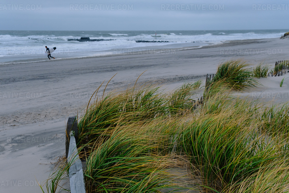 A surfer in Ocean City, New Jersey walking a long a the beach on a gusty fall day. Photo © Robert Zaleski / rzcreative.com