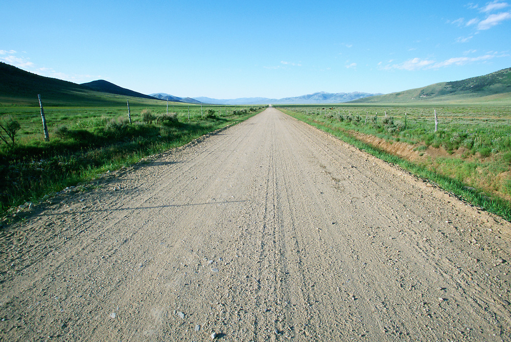 Straight dirt road stretching into distance in rural Southern Idaho USA