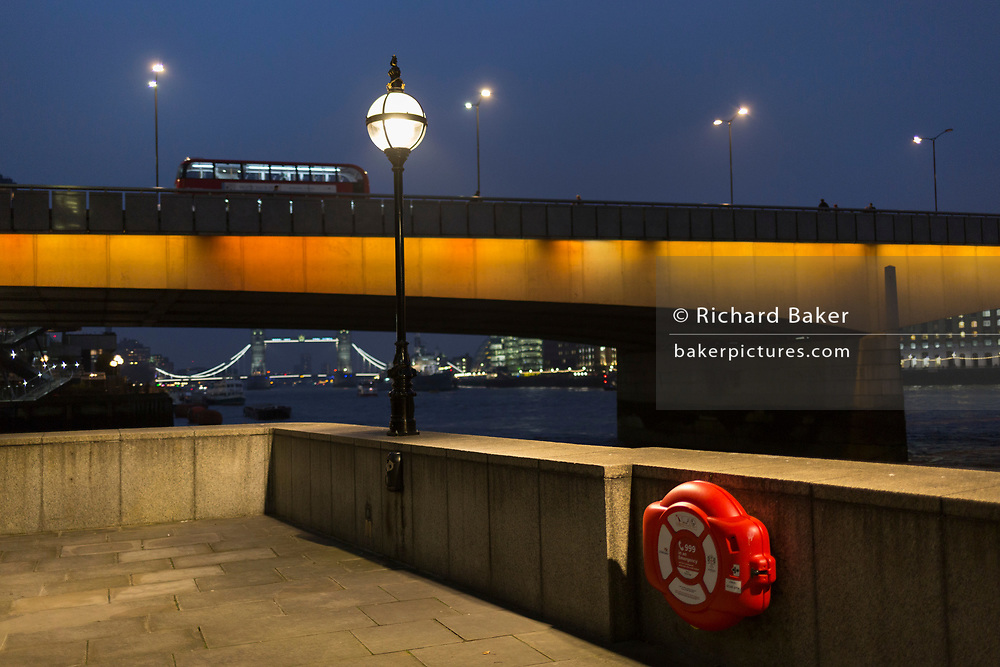 A London bus crosses London Bridge and a life ring overlooking the Thames river on a winter's evening, on 23rd November 2018, in London, England.