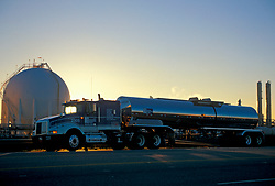 Large liquid transport truck parked outside of a facility at sunset