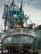 01 OCTOBER 2015 - MAHACHAI, SAMUT SAKHON, THAILAND: A worker in a shipyard repairs a fishing trawler in Mahachai, one of Thailand's largest fishing ports. Thailand's fishing industry had been facing an October deadline from the European Union to address issues related to overfishing and labor practices. Failure to adequately address the issues could have resulted in a ban on Thai exports to the EU. In September Thai officials announced that they had secured an extension of the deadline. Officials did not say how much extra time they had to meet the EU goals. Thailand's overall annual exports to the EU are between 23.2 billion Thai Baht and 30 billion Thai Baht (US$645 million to US $841 million). Thailand's total fish exports were worth about 110 billion baht in 2014.    PHOTO BY JACK KURTZ