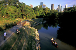 Houston, Texas skyline with people canoeing Buffalo Bayou, a woman walking dogs, and a man bicycling on the Hike and Bike trail.
