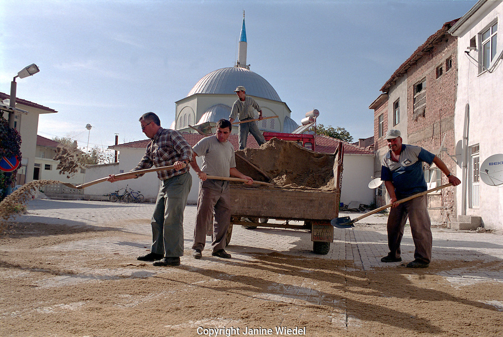 Men doing roadwork infront of mosque in small rural village in South Western Turkey...